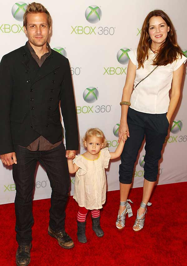 Gabriel Macht and Jacinda Barret holding their daughter's hand