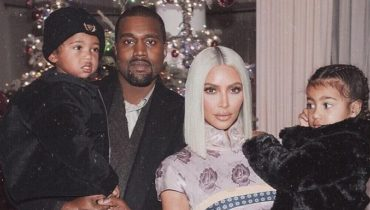 Kanye West is carrying his son Saint West and Kim Kardashian is carrying their daughter North West.