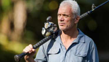 Angler Jeremy Wade is holding a fishing rod and looking away from the camera.