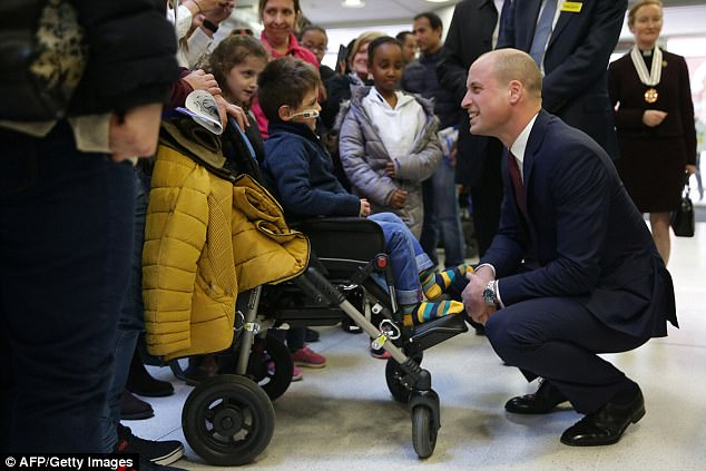 Prince William crouching to talk to a kid in a wheelchair